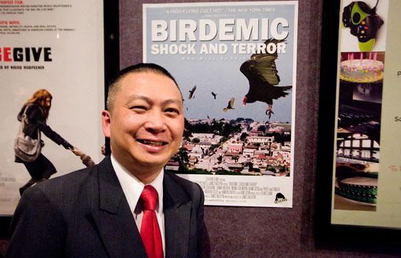 Джеймс Нгуйен рядом с афишей «Птицекалипсиса» в кинотеатре (фотография 2011 года)